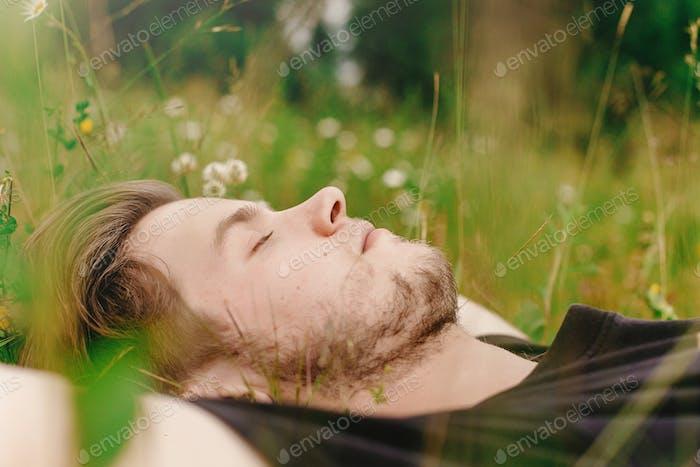 Stilvoller Hipster Mann liegend auf sonnigem Gras
