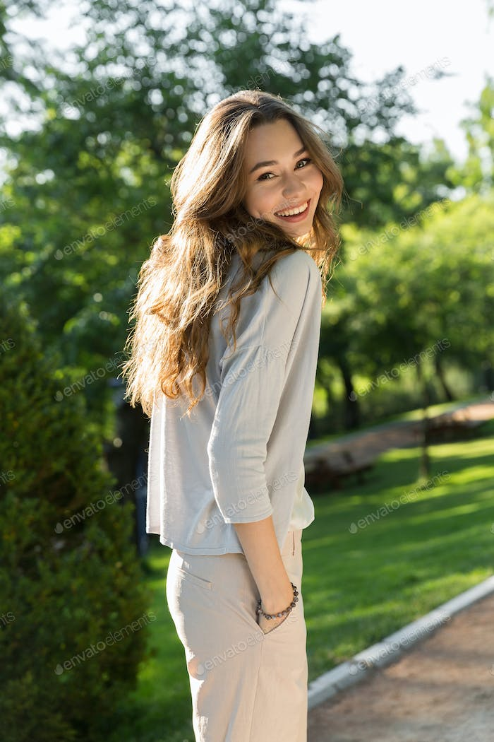 Happy young woman outdoors in park posing