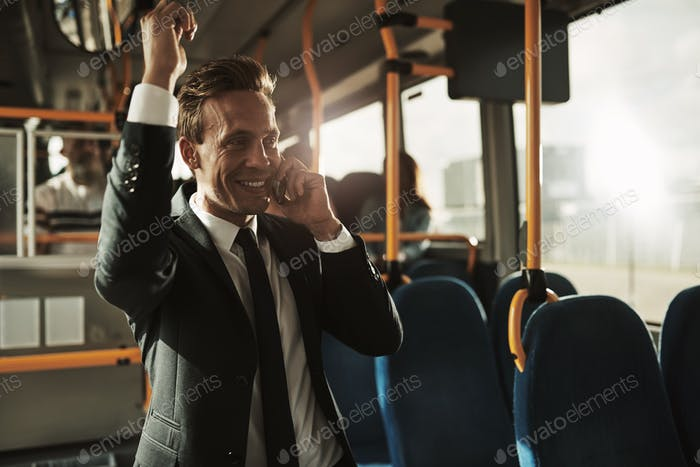 Smiling businessman riding on a bus talking on his cellphone