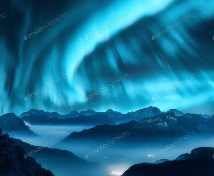 Aurora borealis above mountains in fog at night