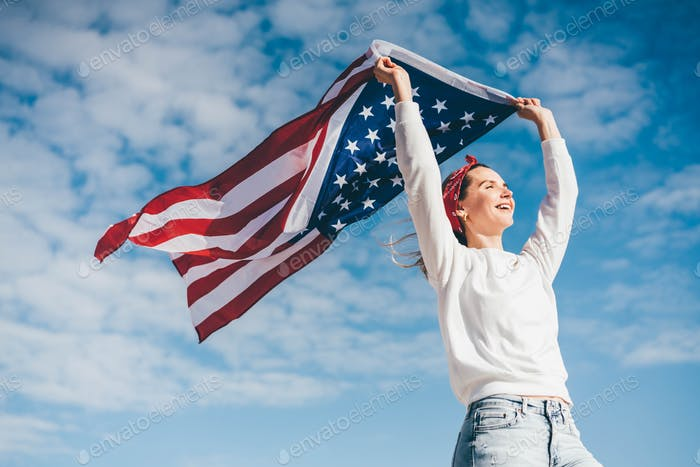 Happy woman holding united states flag against blue sky, independence day concept.