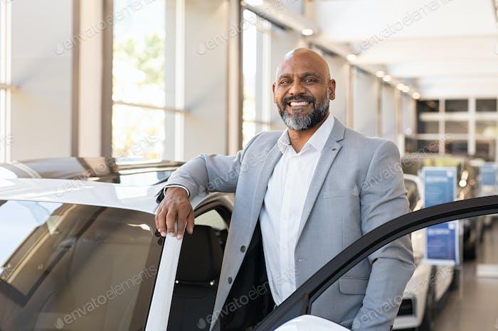 Happy mature black man at car dealership