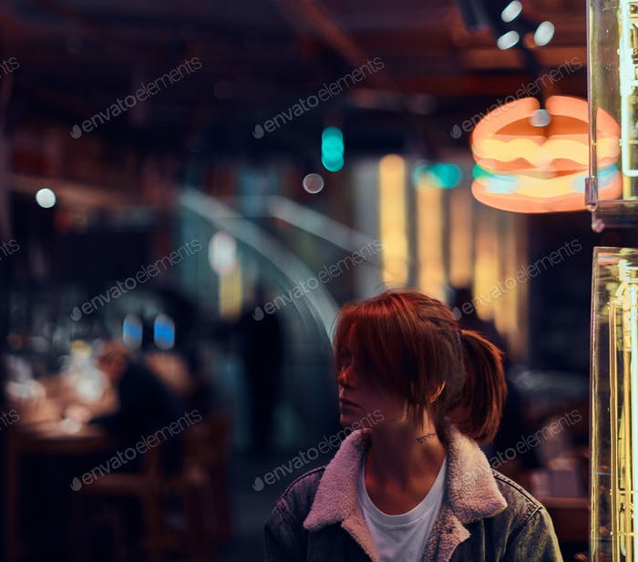 Stylish redhead girl standing in the night on the street. Illuminated signboards, neon, lights.