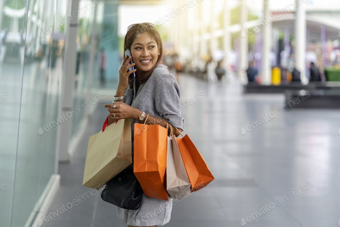 Asian woman using the smart mobile phone for talking with friend to buy some clothes