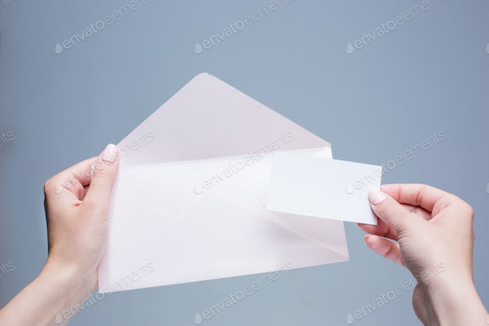 The female hands with envelope against the gray background