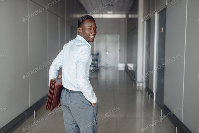 Black businessman with briefcase in office hall