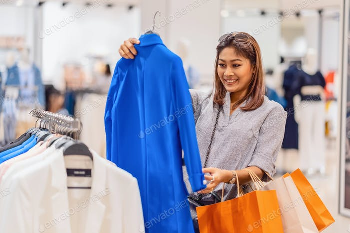 Happy Asian woman choosing clothes in glass store shop with happy action