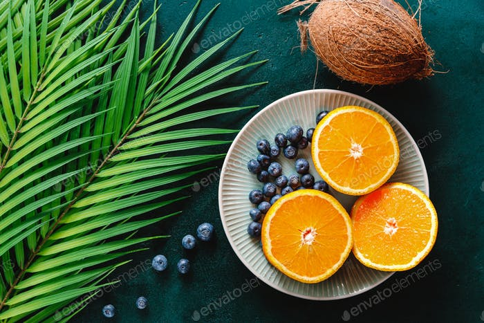 Summer flat lay with palm leaf, oranges and coconu