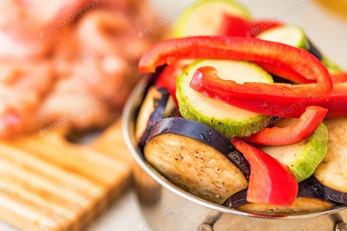Fresh sliced vegetables in metal pan and meat