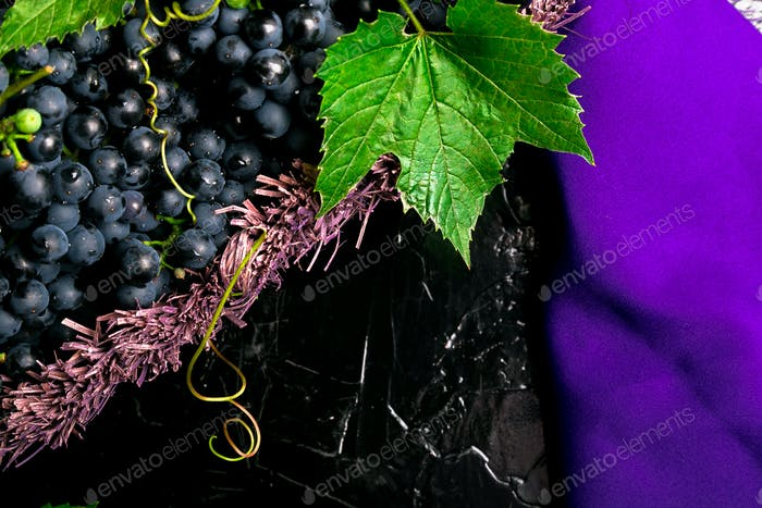 Red wine grapes in voiolet basket on bllack background. Top view. Copy space.