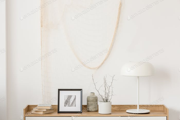White industrial lamp, photo in frame and plant in pot on wooden console table