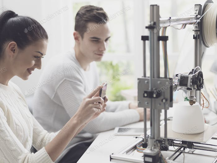 Academic students using a 3D printer in the lab
