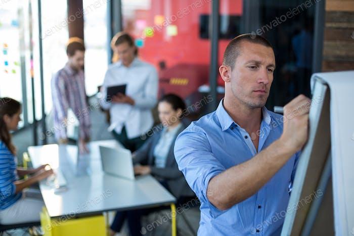 Attentive businessman writing on flip chart
