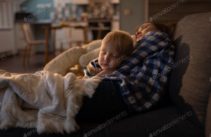 Little cute boy going to sleep on couch with young woman