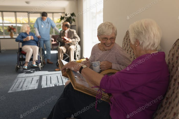 Side view of happy senior women looking photo album and laughing on sofa at home