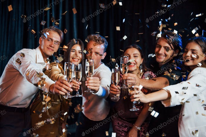 Knocking glasses. Group of friends in festive clothes have party indoors together