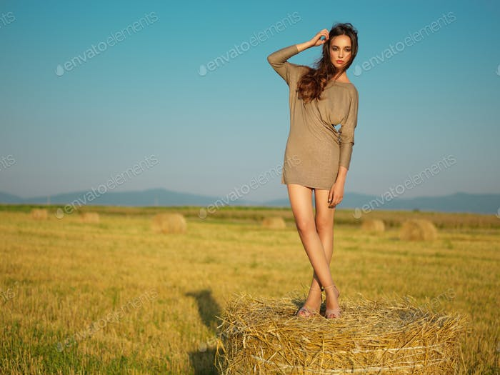 beautiful woman standing on hay stack sunset