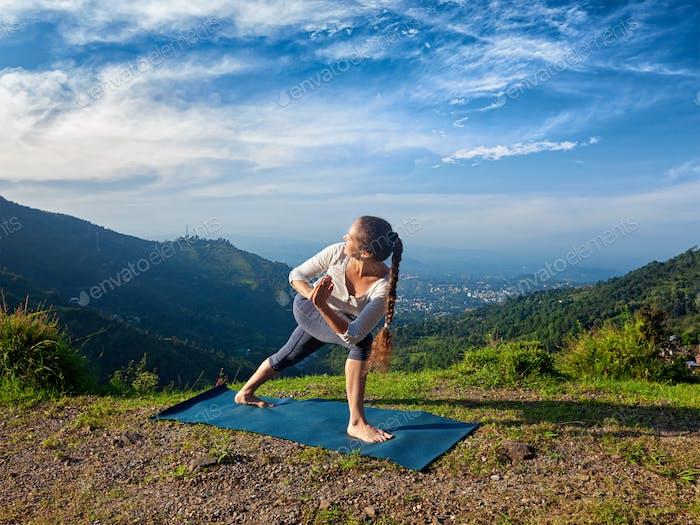 Woman practices yoga asana Utthita Parsvakonasana
