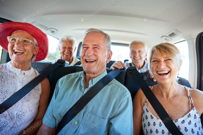 Grupo De Amigos Senior Sentado En La Parte Trasera De Van Ser Impulsado A Vacaciones
