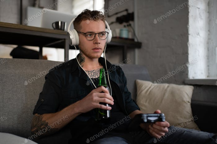 Man drinking beer and playing computer game