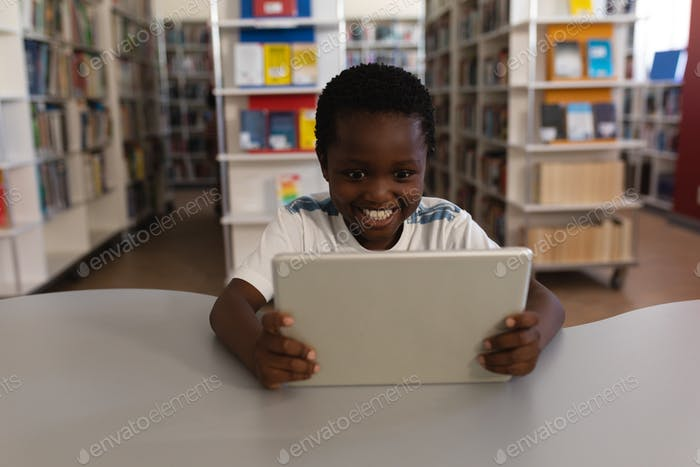Front view of happy schoolboy studying on digital tablet at table in school library