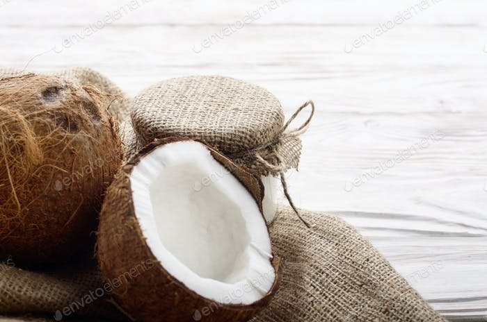 Coconut shell with meat on hemp sackcloth on white wooden kitche