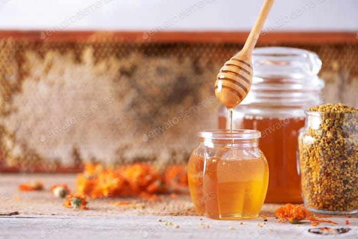 Herbal honey in jar with dipper, honeycomb, bee pollen granules, calendula flowers on grey