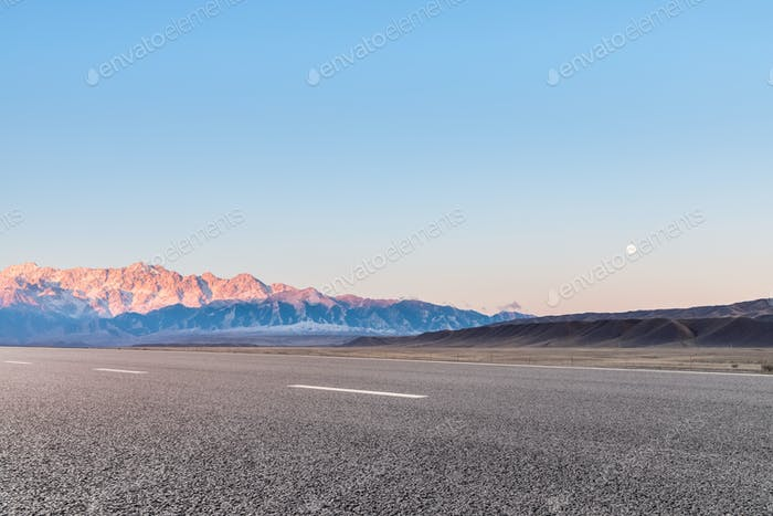 empty asphalt road and mountain was in the golden sunlight