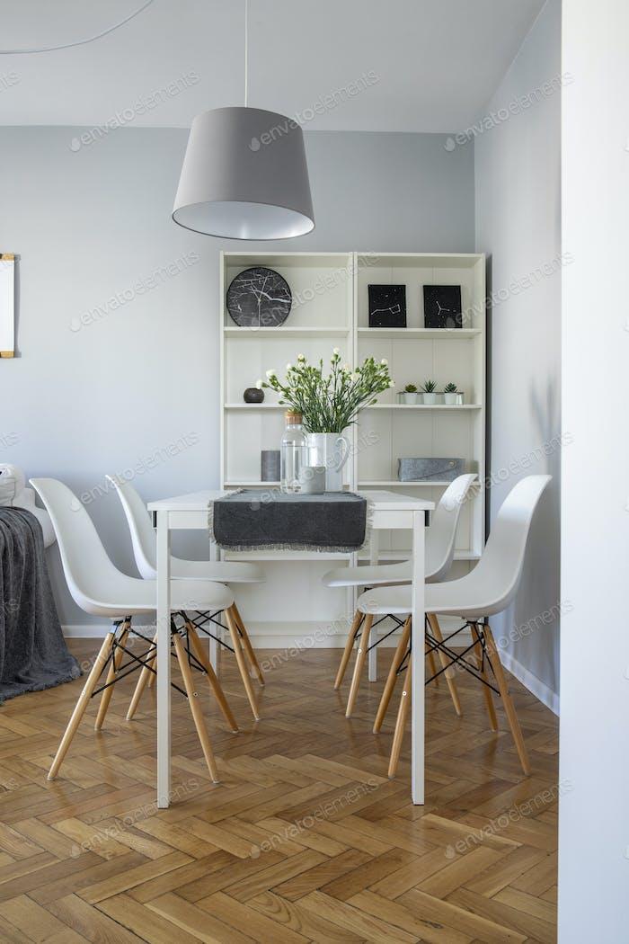 Vertikale Ansicht des skandinavischen Esszimmers mit weißen Holzmöbeln