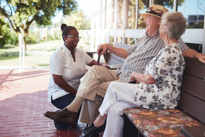 Retired couple relaxing outdoors with female caregiver