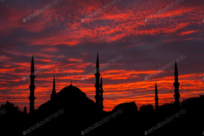 Silhouette of mosque at sunset sky background