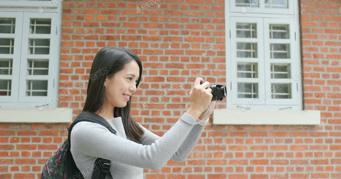 Woman travel and holding digital camera for taking photo