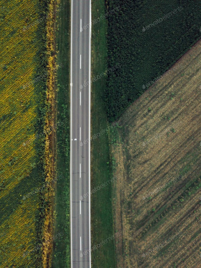 Drone photography of empty road through plain countryside landsc