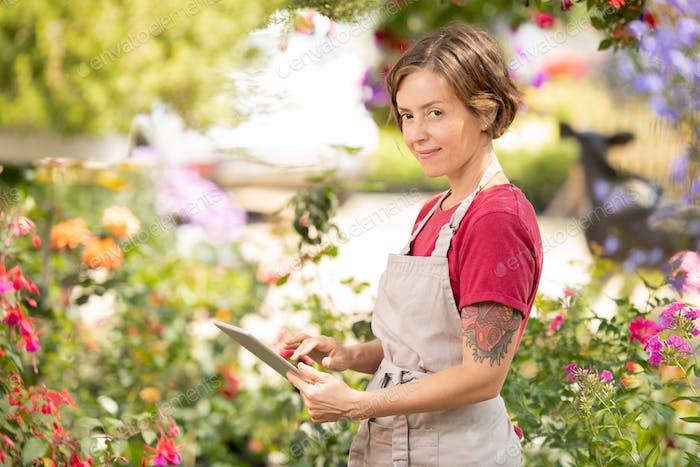 Young positive female flower seller scrolling in tablet for online information