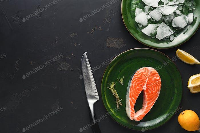 Fresh salmon in green plate at dark background