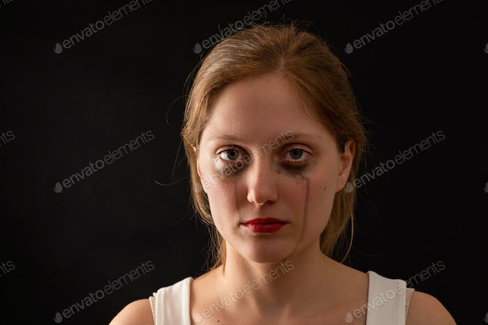 Blonde female with sad expression from front on black background