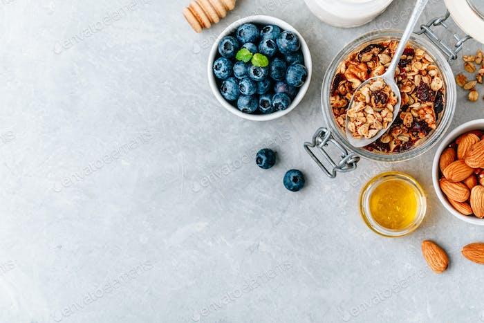 Gesundes Frühstück Müsli mit frischer Heidelbeere, Mandeln und Honig auf grauem Stein Hintergrund