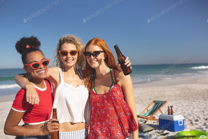Front view of group of young diverse female friends standing together on the beach