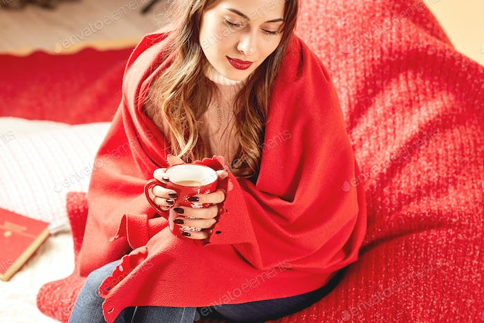 Girl dressed in white knitted sweater and jeans covered in red wrap is sitting with a red cup of hot