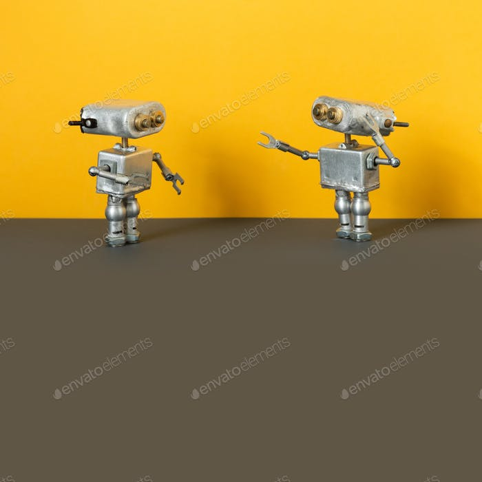 Two simplified metal silver robotics toys on yellow wall