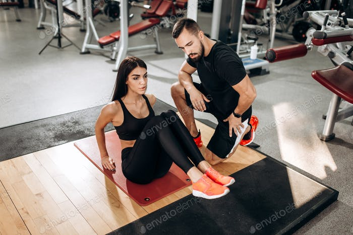 Slim girl dressed in black sports top and tights is doing exercises for the abdominals on the