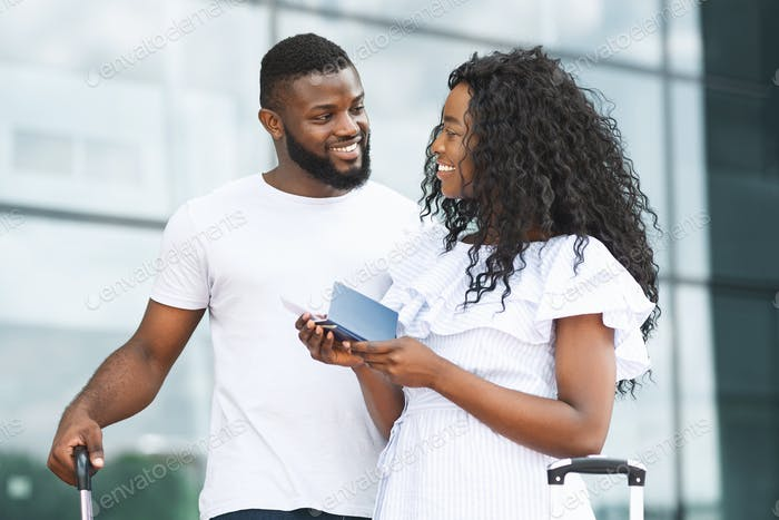 Happy african couple standing at airport building