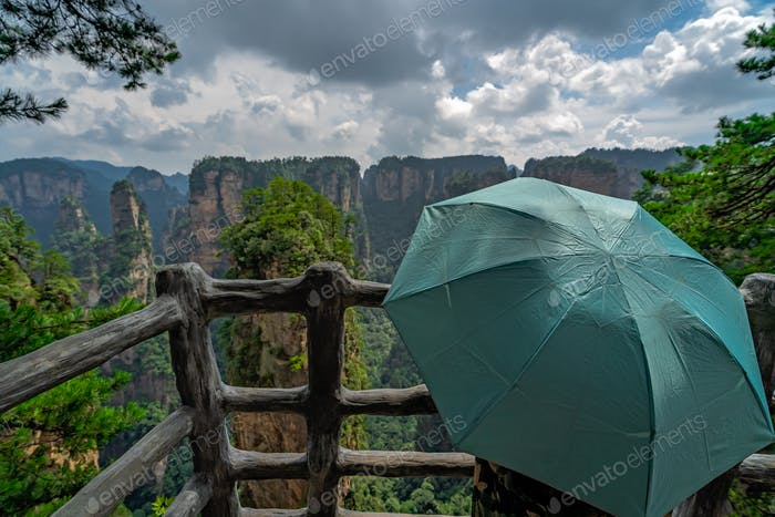 Tourists holding umbrella on the mountain viewpoint