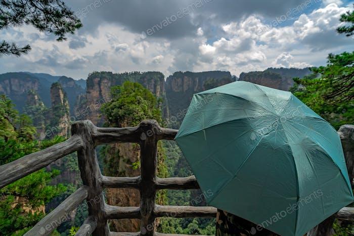 Touristen mit Regenschirm auf dem Bergaussichtspunkt