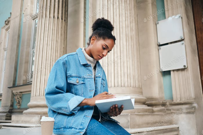 Beautiful African American student girl in denim jacket with book thoughtfully studying outdoor