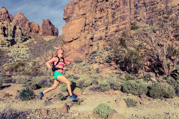 Woman trail running in mountains with backpack