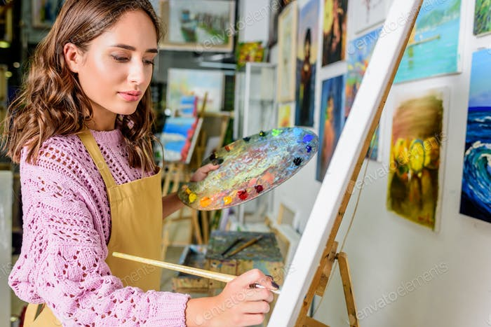 side view of beautiful female artist painting on canvas in workshop