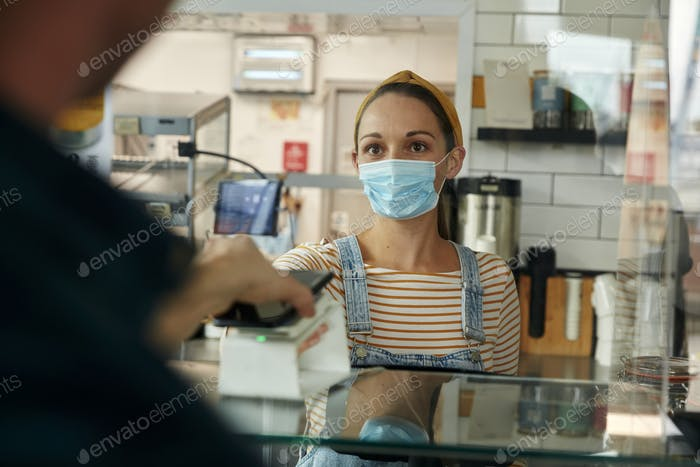 Woman in a face mask with contactless payment terminal