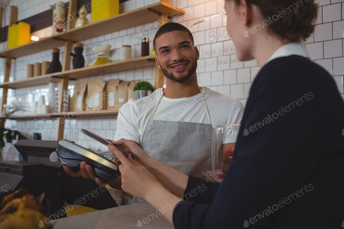 Young waiter showing credit card reader to owner in cafe