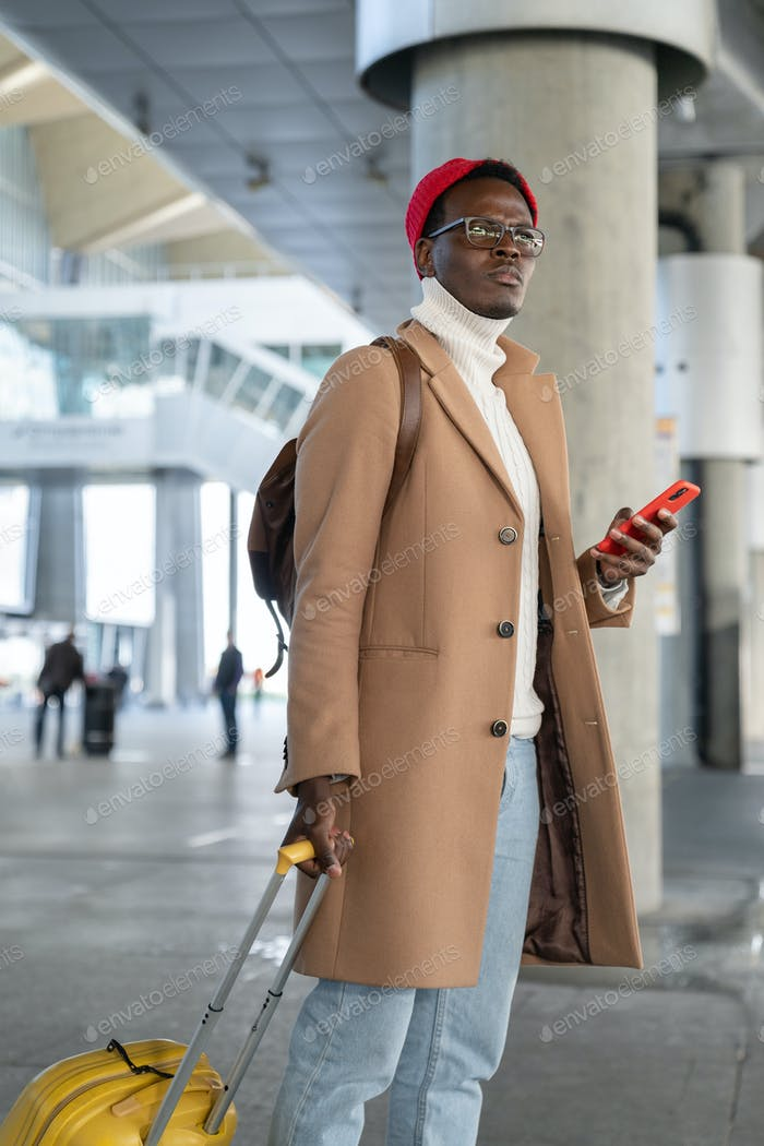 Afro-American traveler man with suitcase holding phone, waiting public transportation in airport